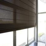 detail hnědé římské rolety na okně